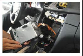 Take out the original CD player and be careful not to stretch the wiring harness behind the assembly