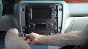 Remove two screws securing the small panel under the factory radio with a screwdriver