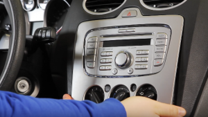 Carefully pry the plastic trim plate with both of your hands, which is in front of the place where the old car radio is situated