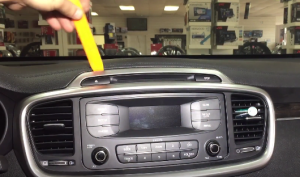 Use a plastic removal tool to remove the car radio trim panel