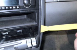 Pry out the trim piece along the perimeter of the center dashboard with a lever