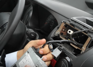 Disconnect the connectors and cables behind to release the original radio
