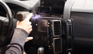 Use a screwdriver to remove the four screws that are holding the car radio