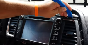 Use the plastic removal tool to pry the air conditioning vents and remove them