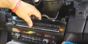 Remove the car radio panel and then disconnect the connectors at the back of it