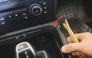 Pop out the panel around the gear shift and then remove this panel