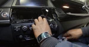 Use a screwdriver to remove the two screws that fix the original car radio dash trim